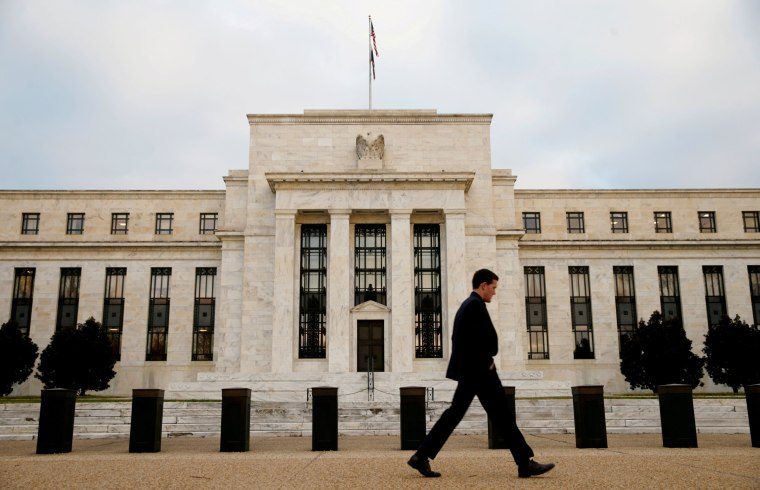 Image: A man walks past the Federal Reserve Bank in Washington DC