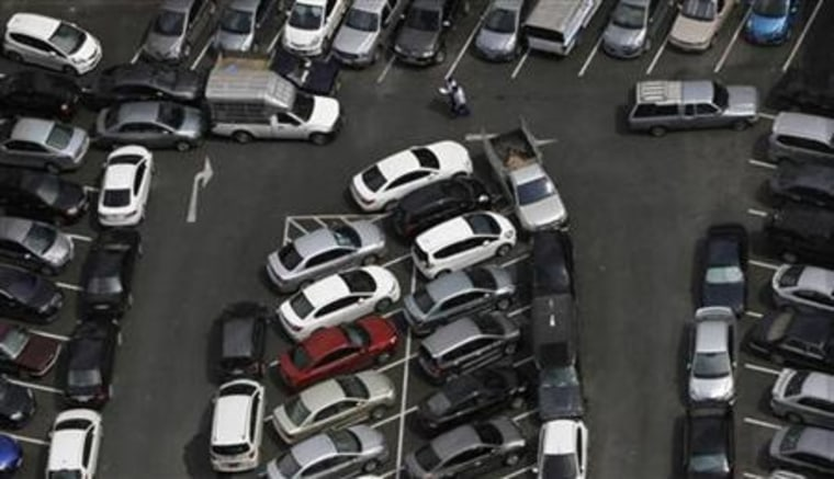 Men walk in a crowded car park in downtown Bangkok