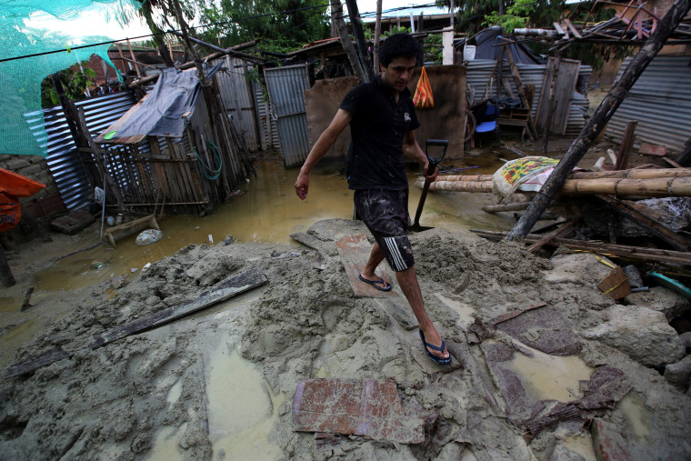 Image: A man walks at his flooded home damaged after heavy rain in Castilla district of  Piura
