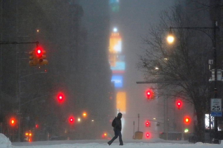 Image: Times Square is seen in the background as a man walks along West 59th street in falling snow in Manhattan, New York