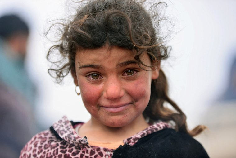 Image: A displaced Iraqi girl, who fled her home, cries during a battle between Iraqi forces and Islamic State militants, near Badush