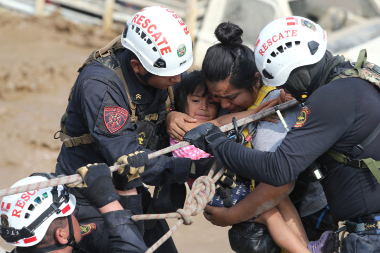 Image: A woman and a child get rescued after a massive landslide and flood in the Huachipa district of Lima, March 17.
