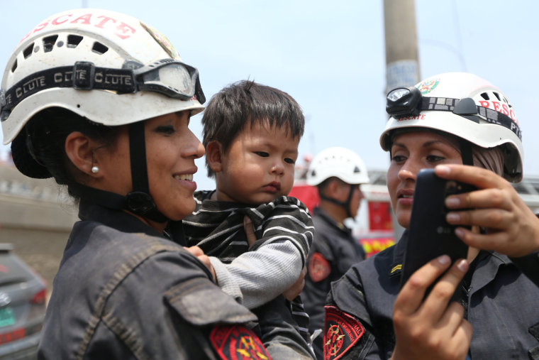Image: Policewomen calm down a child after the massive landslide and flood, March 17.