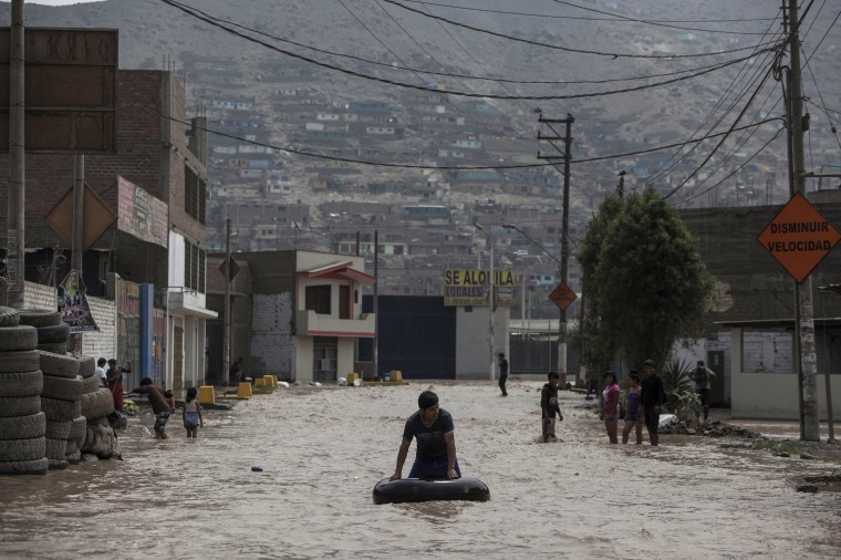 Image: A man plays in a flooded street using an inner tube in Lima, Peru, March 16, 2017.