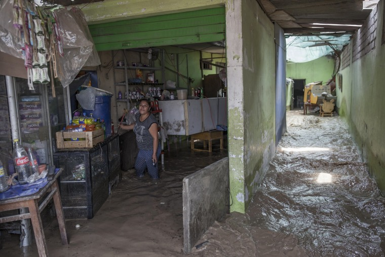 Image: A woman works to salvage belongings from her flooded home, March 16.