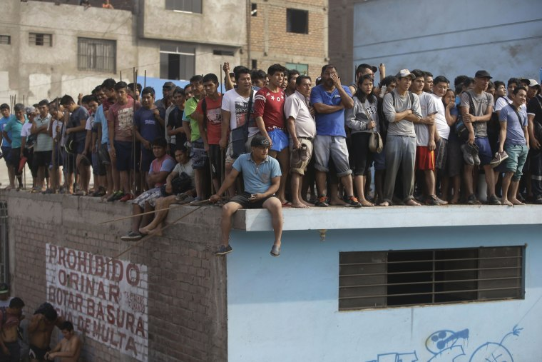 Image: People wait on a rooftop to be rescued from the building surrounded by flood waters, March 17.