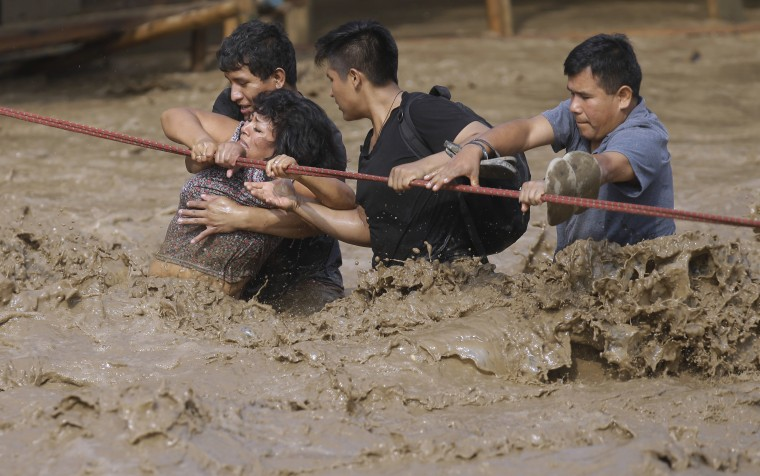 Image: A group of people, stranded in flood waters, hold onto a rope as they walk to safety in Lima, March 17.