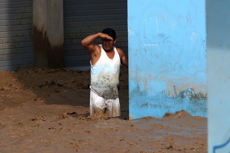 Image: A man stands in a flooded street.