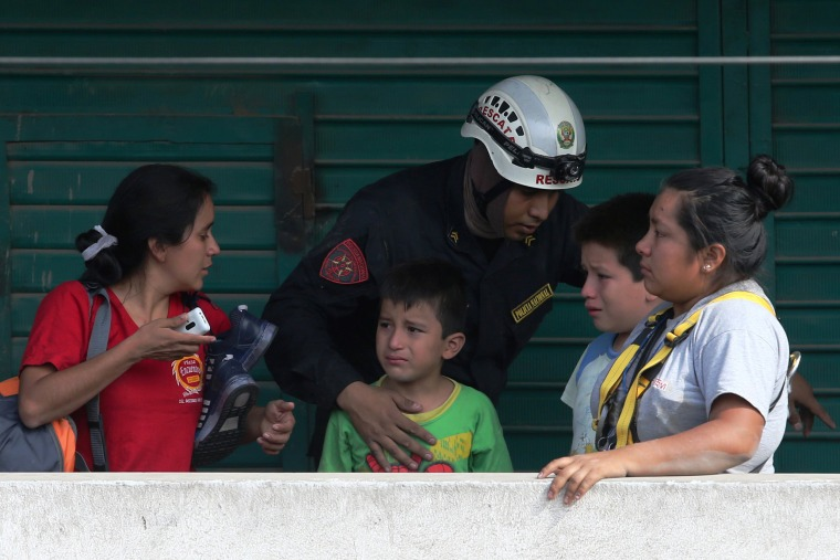 Image: A policeman tries to calm women and children, March 17.