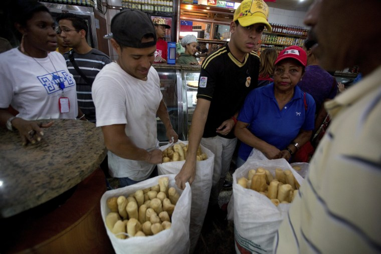 Employees of the Minka state-run bakery carry bags of cheap bread to be distributed to state-run grocery stores in Caracas, Venezuela.