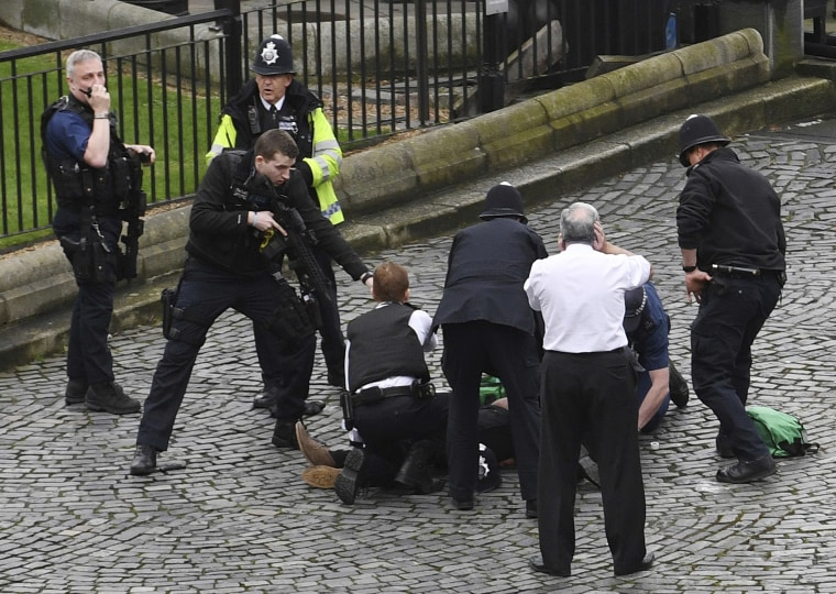 A police officer points a gun at a man on the ground outside the Palace of Westminster on Wednesday.
