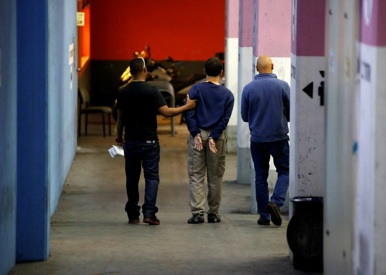 U.S.-Israeli teen arrested in Israel on suspicion of making bomb threats against Jewish community centres in the United States, Australia and New Zealand is escorted by security personnel following his hearing at Magistrate's Court in Rishon Lezion