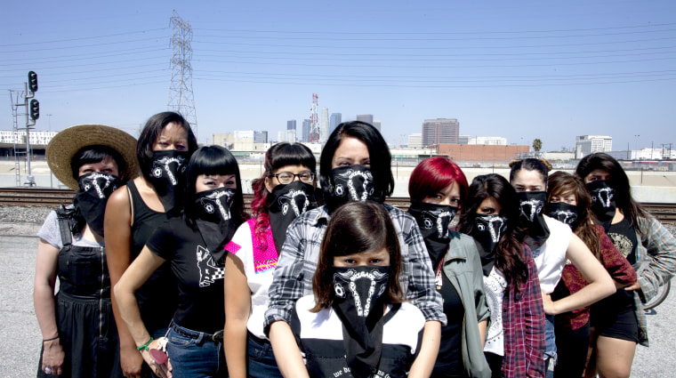 The Ovarian Psycos pose against the backdrop of downtown Los Angeles.