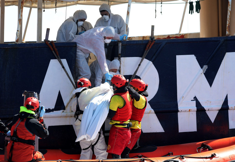 Image: Lifeguards lift the body of a migrant during a search and rescue operation off the Libyan coast