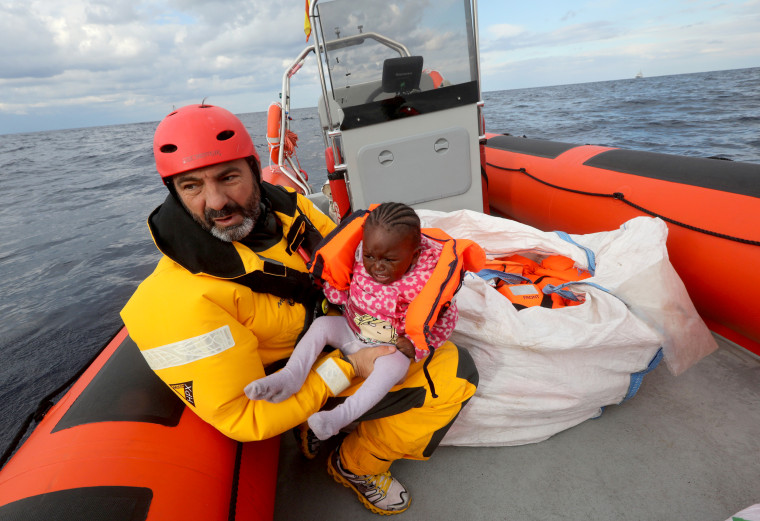 Image: Oscar Camps holds a migrant child inside a rescue craft after pulling it from an overcrowded raft in the central Mediterranean Sea, some 36 nautical miles off the Libyan coast Jan. 2, 2017.