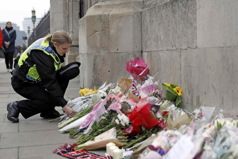 Image: A police officer lays a floral tribute near Westminster Bridge following a recent attack in Westminster, in London