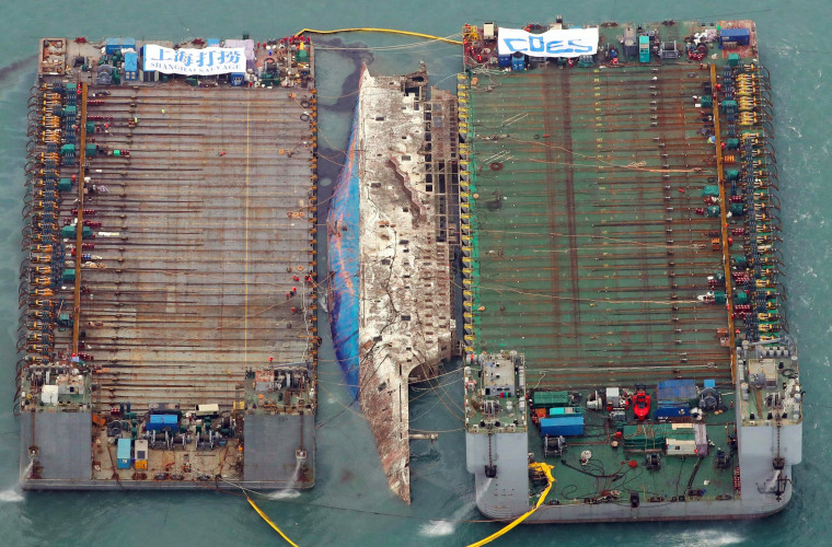 Image: Part of the damaged Sewol ferry sits between two barges after being raised during a salvage operation at sea off the southwestern island of Jindo on March 23, 2017