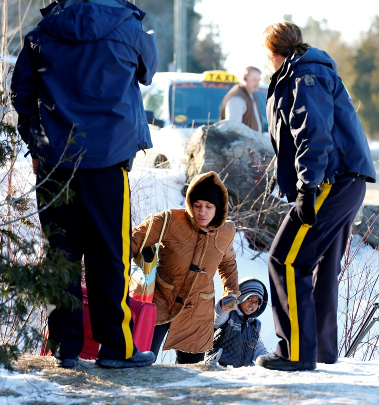 Image: A woman and her child, who claimed to be from Sudan, are met by Royal Canadian Mounted Police (RCMP) officers after they crossed the U.S.-Canada border illegally leading into Hemmingford, Quebec
