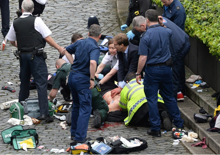 Image: Conservative MP Tobias Ellwood (centre, in group at bottom right) helps emergency services attend to a police officer at the scene outside the Palace of Westminster, London