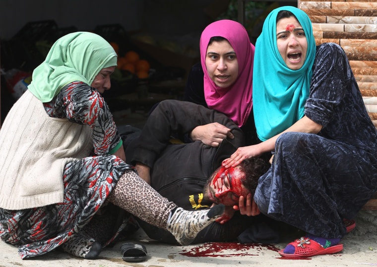 Image: Iraqi women cry over their brother's body, who was killed by a mortar shell fired by Islamic State (IS) group jihadists on civilians who were gathered to receive aid, in Al-Risala neighbourhood