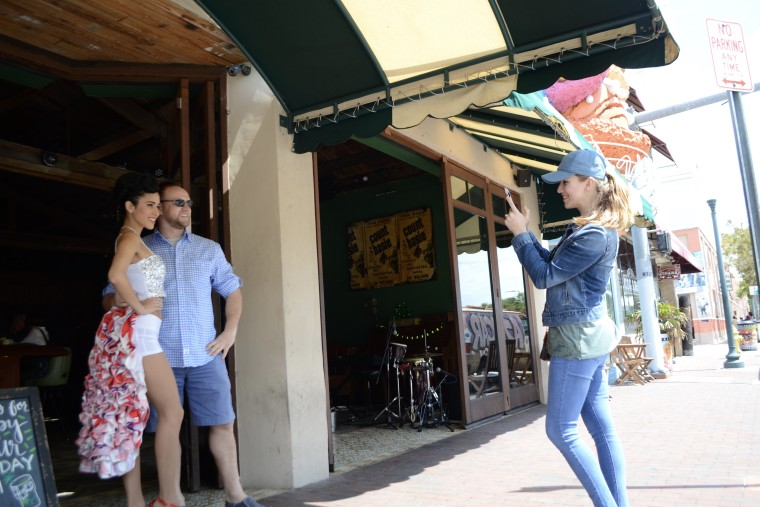 Lana Serhiyenia takes a picture of Steve Lenkov outside the restaurant Ball and Chain. Sehiyenia and Lenkov are orginally from Belarus but now live in Philadelphia. They are on vacation in South Beach but spent an afternoon in Little Havana.