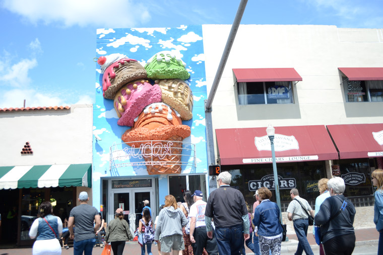 Tourists cross the street in front of the popular Azucar ice cream shop.
