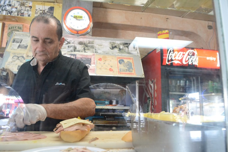 """Juan Robaina, manager of  """"El Pub,"""" is a master at preparing sandwiches, especially the iconic """"cubanos."""" He says many tourists view the restaurant website before heading there and already know what they're ordering."""
