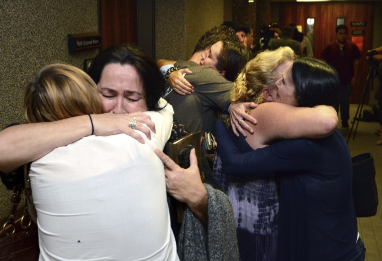 """Carly """"Charli"""" Scott's family and friends embrace outside the courtroom after guilty verdicts were announced for Steven Capobianco in Wailuku, Hawaii on  Dec. 28, 2016."""