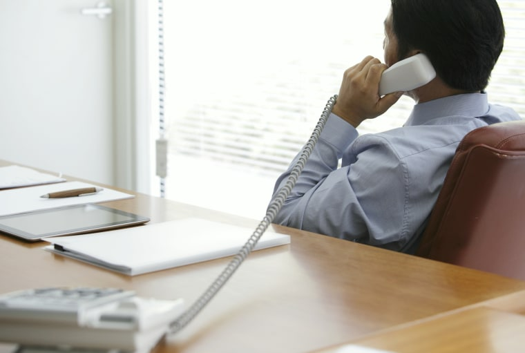 Mature businessman talking on phone in office