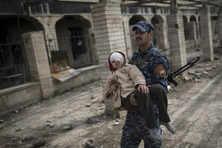 Image: A Federal Police officer carries an injured boy through a destroyed train station during fighting between Iraqi security forces and Islamic State militants, on the western side of Mosul, March 19.