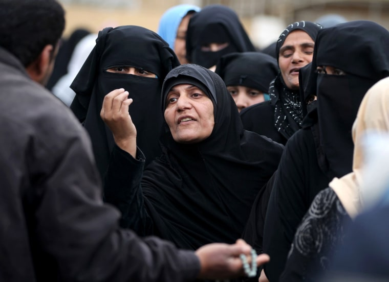 Image: An Iraqi woman gestures as she queues to receive aid in the Al-Risala neighborhood on March 22.