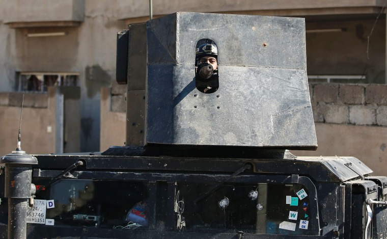 Image: A member of the Iraqi forces mans a turret mounted atop a humvee as troops advance towards the Old City in western Mosul on March 24.