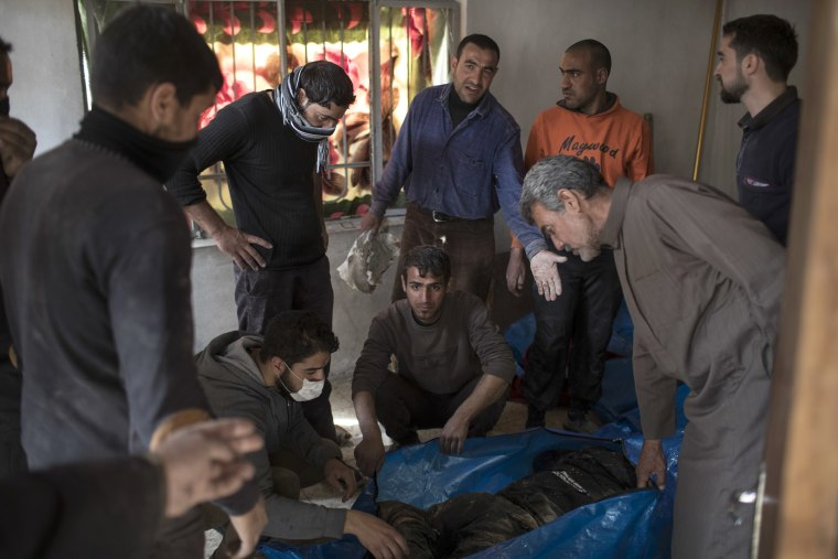 Image: Residents gather around the body of a men killed after a house was destroyed, March 24.