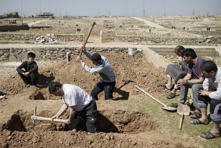 Image: Relatives and friends dig the graves of two civilians killed during fighting, March 25.