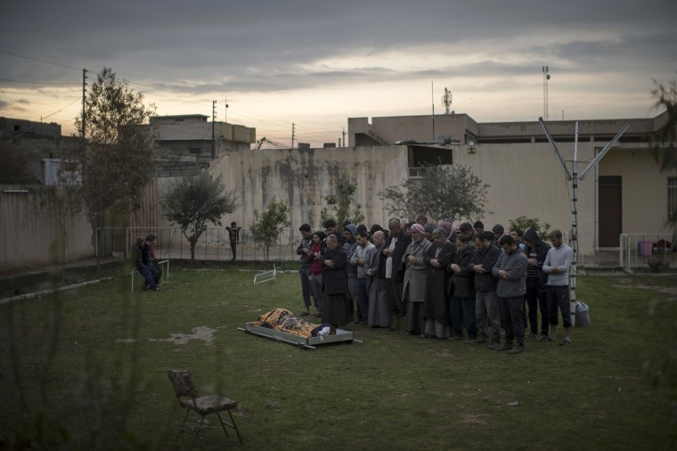 Image: Relatives and friends pray next to the body of Suheyil Najn Abdullah after he was killed by a sniper trying to flee fighting between Iraqi security forces and Islamic State on the western side of Mosul, March 23.