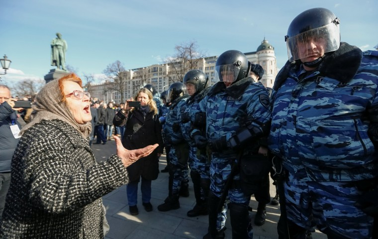 Image: A woman argues with law enforcement officers as they block the rally in Moscow.