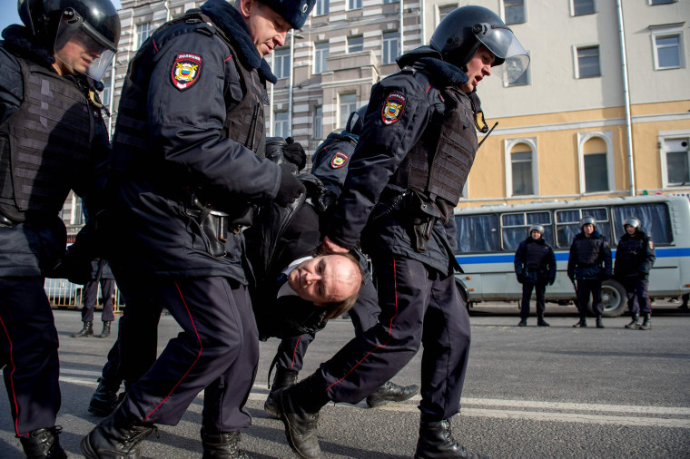 Image: Police officers detain a man during an unauthorized anti-corruption rally in central Moscow.