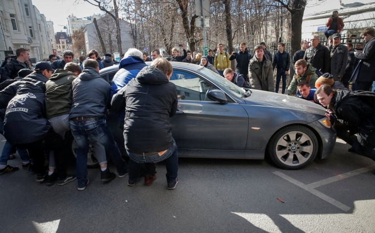Image: Opposition supporters move a car to block the road to prevent the van transporting detained anti-corruption campaigner and opposition figure Alexei Navalny.