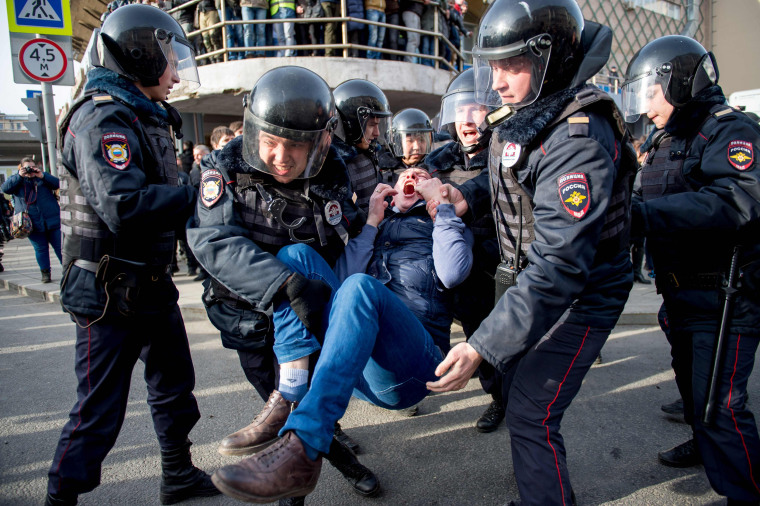 Image: Riot police officers detain a protester.