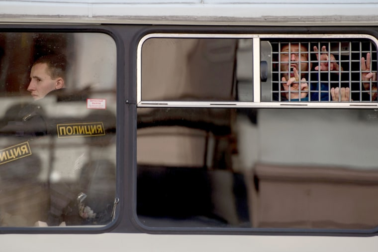 Image: Protesters gesture from a police bus after being detained.