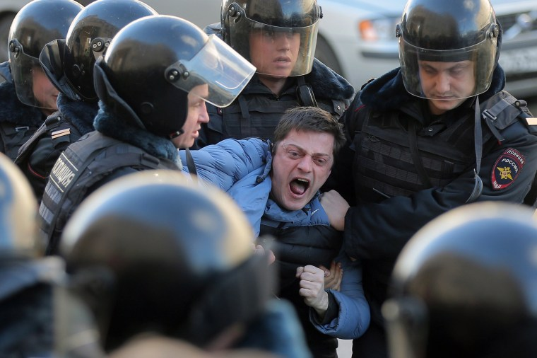 Image: Russian riot policemen detain one of dozens of demonstrators.