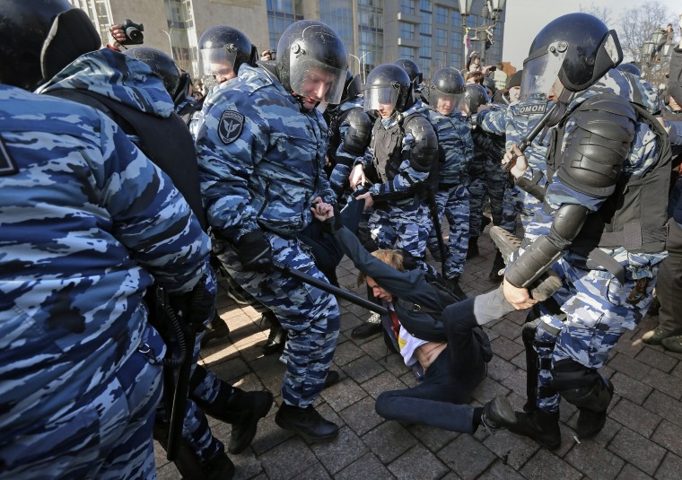 Image: Policemen detain protesters.