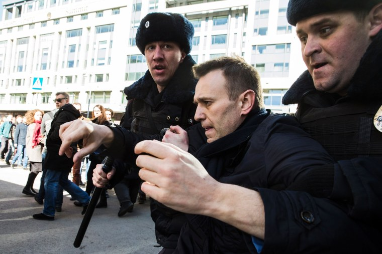 Image: This handout photo from Alexei Navalny's campaign shows police officers detaining Kremlin critic Alexei Navalny during an unauthorized anti-corruption rally in central Moscow.