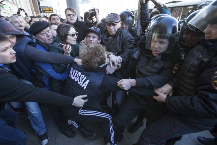 Image: Police and protesters fight over another demonstrator, who was detained in downtown Moscow.