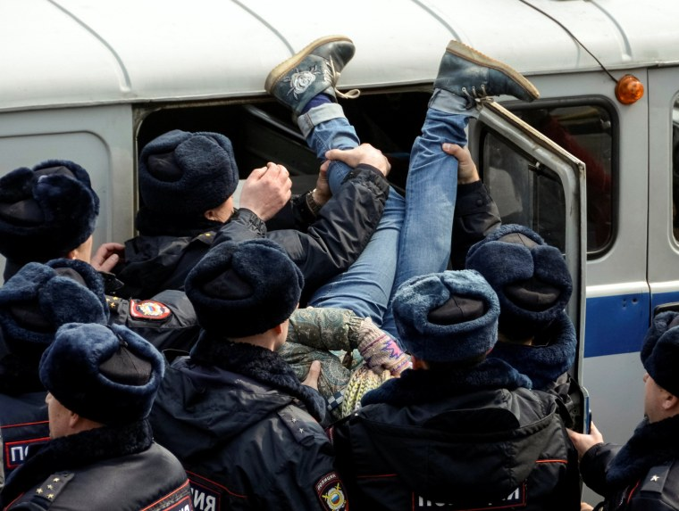 Image: An opposition supporter is seen being put into a police truck feet first, during a rally in Vladivostok.