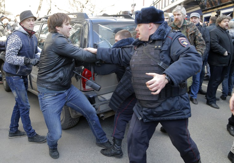 Image: A Russian policeman tries to stop a protester from pushing a vehicle as demonstrators block a street in order to obstruct the transit of a police bus carrying detained Alexei Navalny.