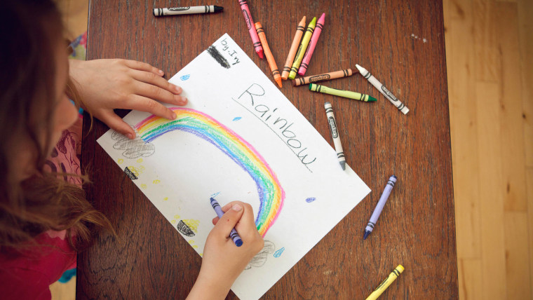 girl drawing rainbow with crayons