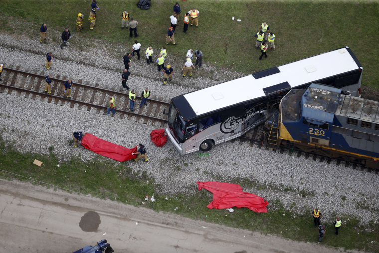 Image: Responders work the scene where a train hit a bus in Biloxi, Mississippi