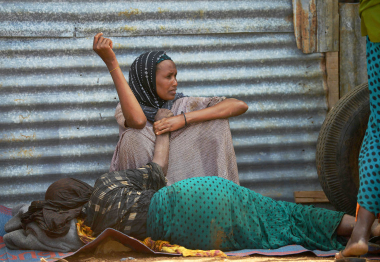 Image: An elderly woman weakened by hunger lies on the ground as her daughter watches over her at the camp, March 15.