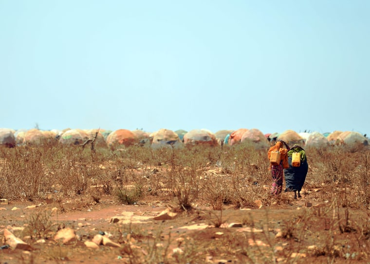 Image: Women carrying jerrycans of water from a collection point set up by a UN aid agency walk on March 14 toward the camp.